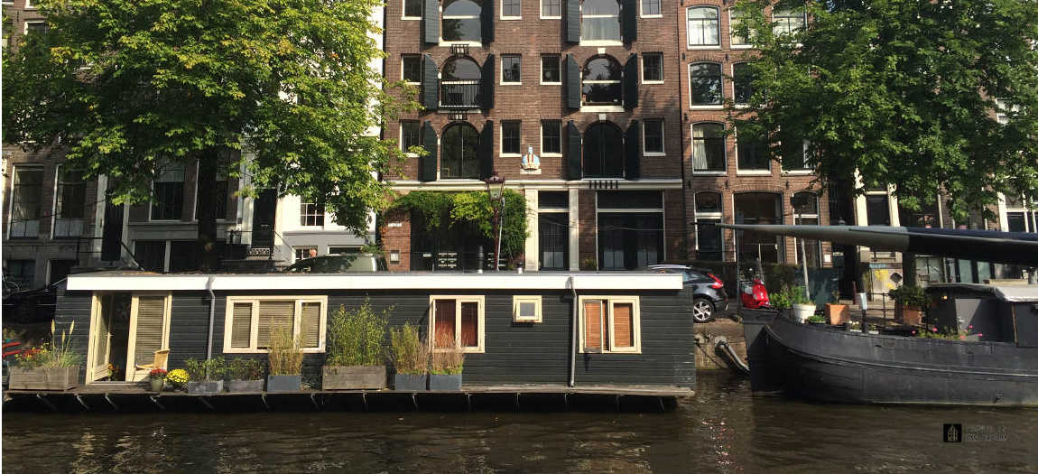 Typical housebaot in a canal in Amsterdam